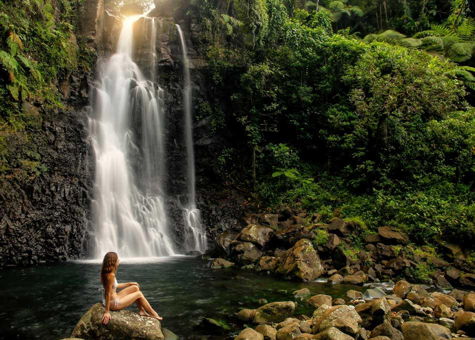 Young woman sitting by Middle Tavoro Waterfalls in Bouma National Heritage Park on Taveuni Island, Fiji